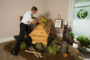 Lars Oerding schmückt einen aufgebahrten Sarg - Oerding Bestattungen Zeven